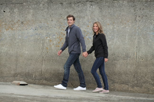 Man and woman walking, wearing jeans and polar jackets.